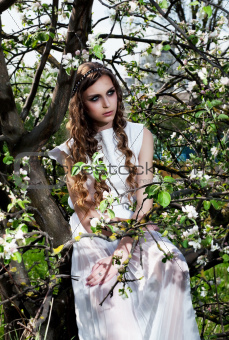 Blossom. Blooming nature and pretty girl sitting