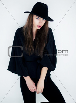 Stylish young female in fashion clothes posing