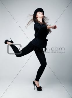 Elation. Active woman shopper in black hat. Studio shot