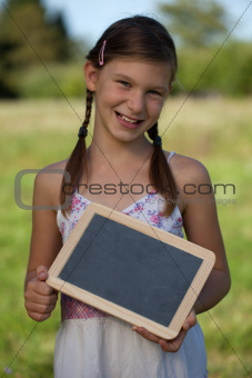 Young girl holding a small blackboard