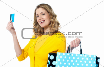 Attractive woman holding cerdit-card with shopping bags
