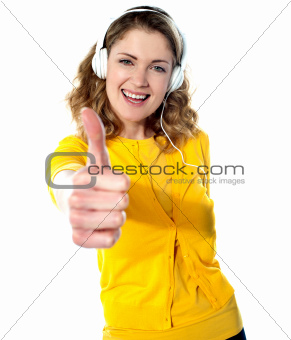 Thumbs-up woman enjoying music