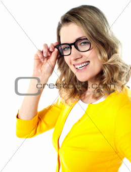 Smiling caucasian woman wearing and holding her glasses