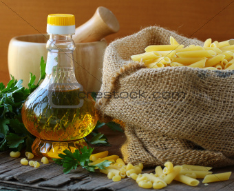 Linen bag of pasta (penne) and a bottle of oil on wooden table
