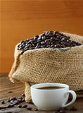 Linen bag of coffee beans and a cup of espresso on a wooden table