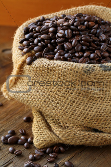 linen bag with coffee beans on wooden table