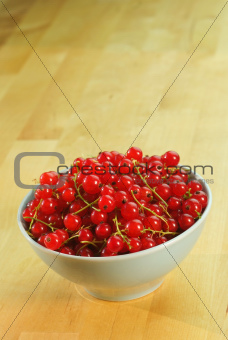 Red currant fruits in a bowl on a wooden table