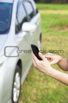 hand touching the smart phone before a car and calling for help