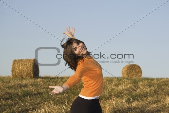 Beautiful woman open is arms  in a field with hay bales