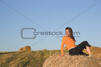 Beautiful woman in a field with hay bales