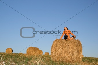 Beautiful woman seated in hay bale