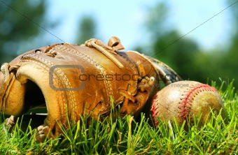 Old baseball glove and ball on the grass