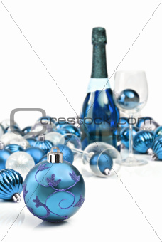 Blue Christmas ornaments with a bottle of sparkling wine