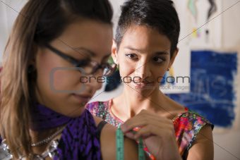 Fashion designer using measuring tape with client