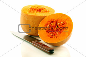 Two halves of a ripe pumpkin and a table knife.