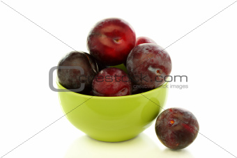 Ripe plums in green bowl.