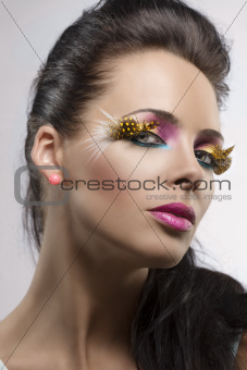 girl with feathered makeup turned at left