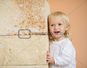 Portrait of baby leaning against wall