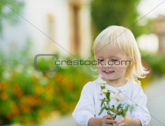 Portrait of baby with flowers outdoors