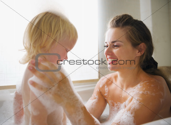 Mother washing with baby in bathtub