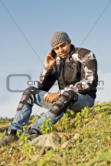 Man sat at roadside using cell phone