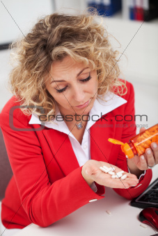 Tired woman taking pills in office