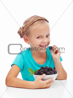 Happy girl eating fresh blackberry
