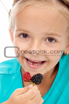 Little girl eating blackberries