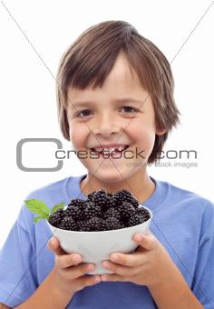 Happy boy with blackberries