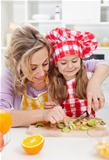 Woman and little girl making fresh fruits snack together