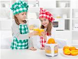 Little chefs making fresh orange juice in the kitchen