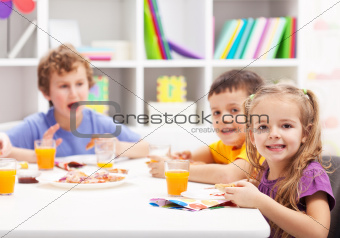 Childhood friends eating together in kids room
