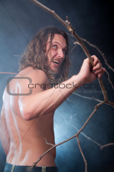 Screaming long haired naked man in the forest