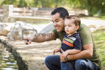 Happy Hispanic Father Points with Mixed Race Son at the Park Pond.