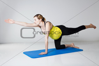 Pregnant woman exercising on mat