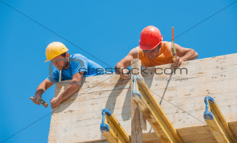 Construction workers nailing cement formwork in place