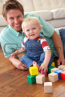 Father And Son Playing With Coloured Blocks At Home