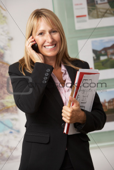 Portrait Of Female Estate Agent In Office On Phone