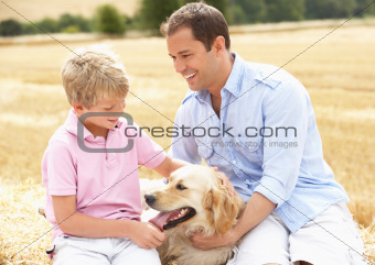 Father And Son Sitting With Dog On Straw Bales In Harvested Field
