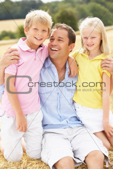 Father And Children Sitting On Straw Bales In Harvested Field