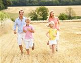 Family Running Together Through Summer Harvested Field