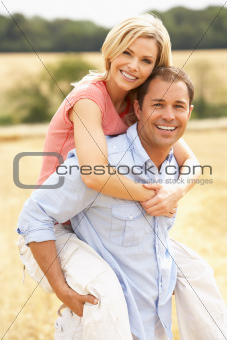 Couple Having Piggyback In Summer Harvested Field