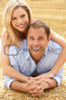 Couple Relaxing In Summer Harvested Field