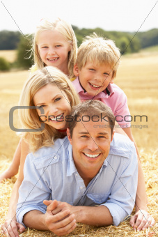 Family Relaxing In Summer Harvested Field