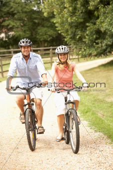 Couple Cycling In Countryside Wearing Safety Helmets