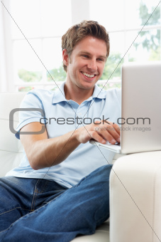 Man Sitting On Sofa Using Laptop At Home