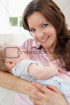 Close Up Of Affectionate Mother Cuddling Baby Boy At Home