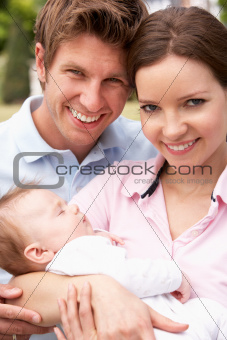 Parents Cuddling Newborn Baby Boy Outdoors At Home