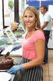 Woman Working Behind Counter In CafŽ Slicing Cake