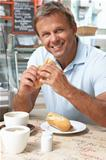 Male Customer Enjoying Sandwich And Coffee In CafŽ